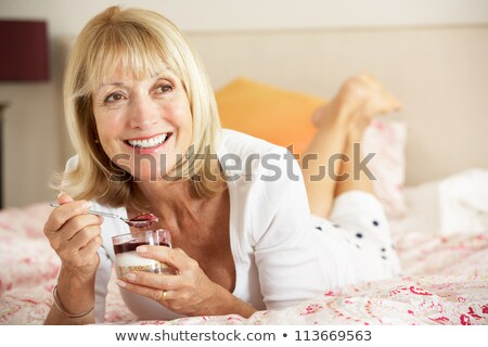 senior woman eating pudding stock photo © is2
