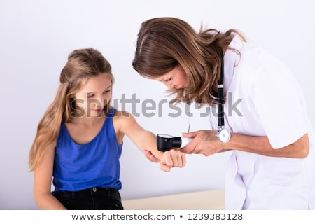 Female Doctor Examining Skin Of Girl Stock photo © AndreyPopov