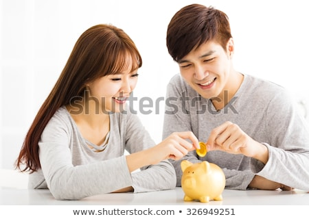 Happy Young Woman Inserting Coin In Piggybank Stock photo © AndreyPopov