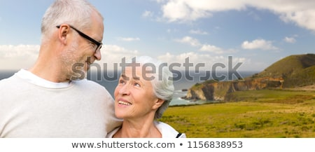 happy senior couple hugging over big sur coast Stock photo © dolgachov