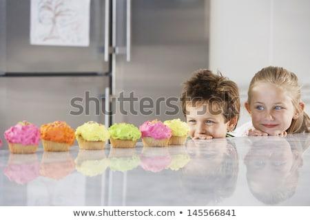 Lány néz minitorta konyhapult mosolyog aranyos Stock fotó © AndreyPopov