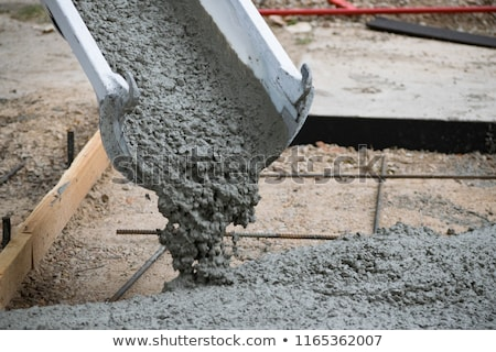 construction worker smoothing wet cement with trowel tools stock photo © feverpitch
