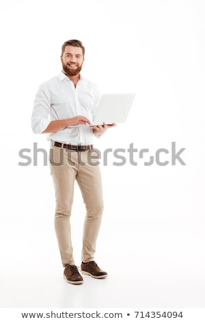 Stock photo: Handsome young bearded man standing isolated over white wall background holding present gift box.