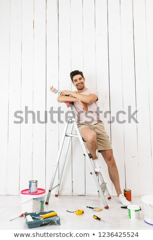 Full length photo of smiling guy 20s standing on ladder and pain Stock photo © deandrobot