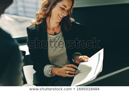 woman looking at report holding by her coworker stock photo © andreypopov