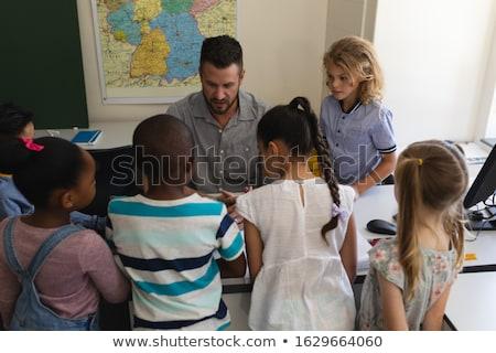 Front view male Caucasian school teacher teaching schoolkid on laptop at desk and all schoolkids par Stock photo © wavebreak_media