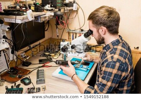 Man with electric handtool looking in microscope during work with tiny details Stock photo © pressmaster