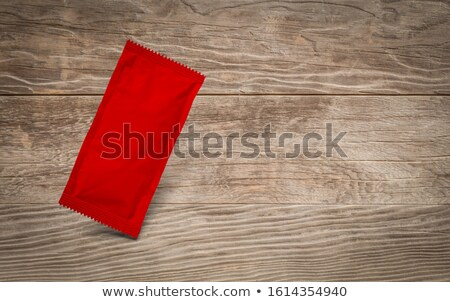 Blank Red Condiment Packet Floating on Aged Wood Background Stock photo © feverpitch