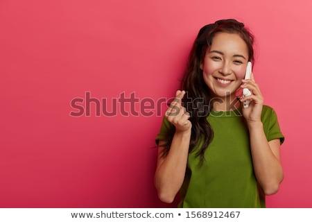 Indoor shot of positive lovely woman has telephone conversation, keeps mobile phone near ear, focuse Stock photo © vkstudio