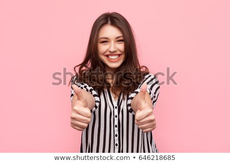 Glamourous teenager gesturing thumbs-up Stock photo © stockyimages