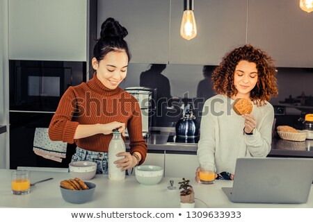Dark-haired woman eating cereal in her bedroom Stock photo © wavebreak_media
