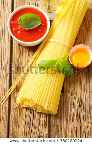 Bundle of dried spaghetti, tomato passata and egg Stock photo © Digifoodstock