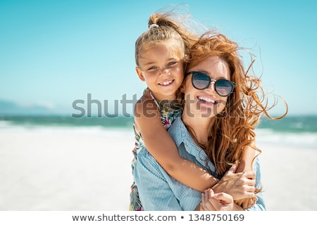 Happy mother having fun with her daughter at the beach Stock photo © deandrobot