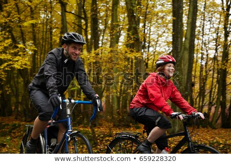Couple cycling surrounded by trees Stock photo © IS2