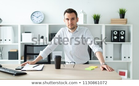 a young man stands in the office near the table and puts his hands on him stock photo © traimak