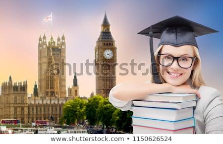 graduate in mortarboard with books over london Stock photo © dolgachov