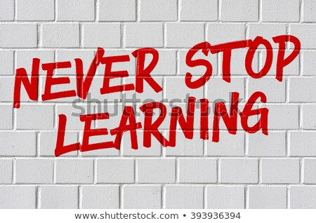 Сток-фото: Never Stop Learning On White Brickwall Motivational Concept