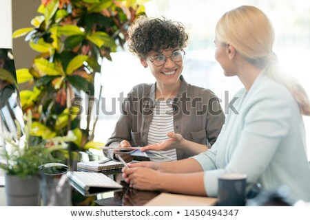 Pretty young designer interacting to one of clients Stock photo © pressmaster