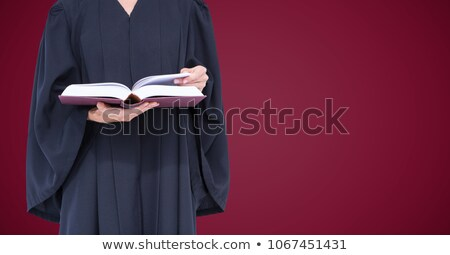 Judge mid section with open book against maroon background Stock photo © wavebreak_media