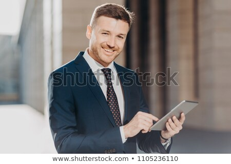 Photo of successful male banker does remote work on digital tablet, has happy expression, dressed in Stock photo © vkstudio