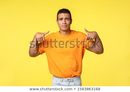 Upset, sad cute handsome caucasian guy in orange t-shirt, pointing fingers down, gesturing to turn a Stock photo © benzoix