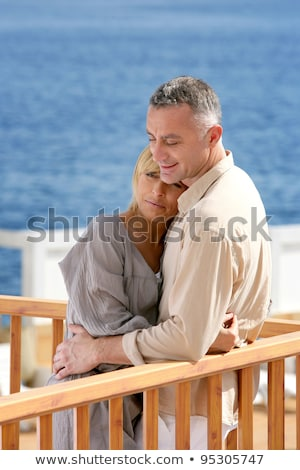middle aged couple stood on balcony overlooking the sea stock photo © photography33