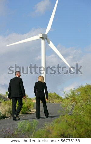 Man and woman in suit walking next to a wind turbine Stock photo © photography33