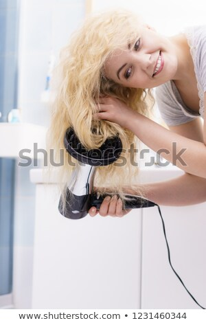 Blonde woman using a hairdryer Stock photo © photography33