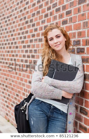 Portrait of a smiling student holding her binder while looking at the camera Stock photo © wavebreak_media