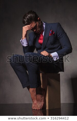 thoughtful young business man sitting on a wood box stock photo © feedough