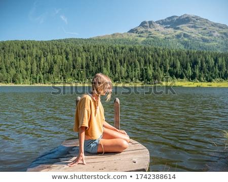 beautiful girl sitting on the pier stock photo © tekso