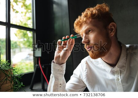 Portrait of young concentrated readhead bearded man, sitting at  Stock photo © deandrobot