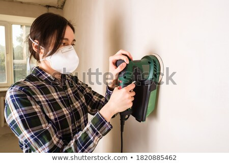 Woman polishing wall with sandpaper  Stock photo © dash