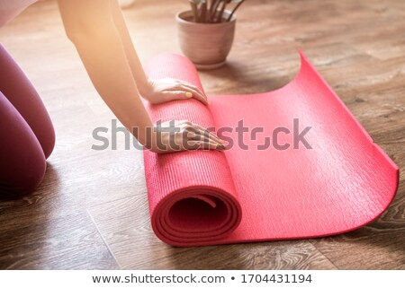 Cropped image of a young woman unrolling fitness mat Stock photo © deandrobot