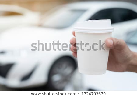Woman's hand taking coffee cup from the car holder Stock photo © Kzenon