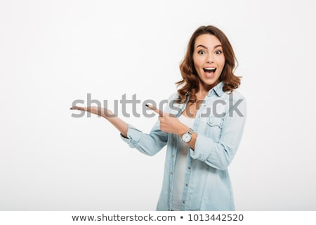 portrait of a happy young casual girl pointing stock photo © deandrobot