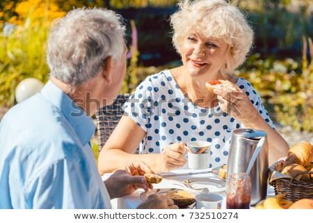 Happy elderly couple eating breakfast in their garden outdoors Stock photo © Kzenon