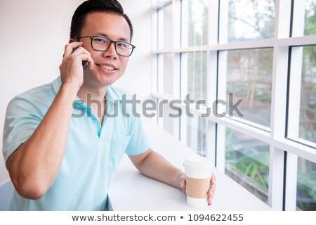 Portrait of smart business man 30s in white shirt talking on cel Stock photo © deandrobot