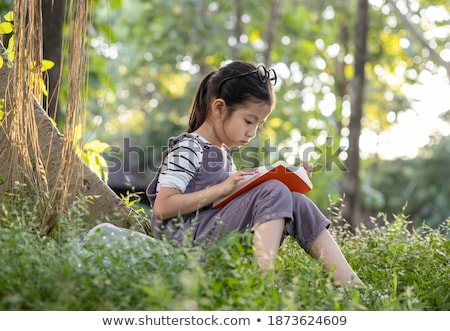 Young smiling asian girl relax under big tree in the park on hol Stock photo © Freedomz