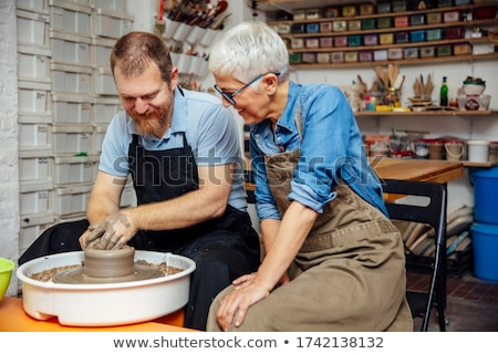 Senior woman spinning clay on a wheel with teacher at pottery cl Stock photo © boggy