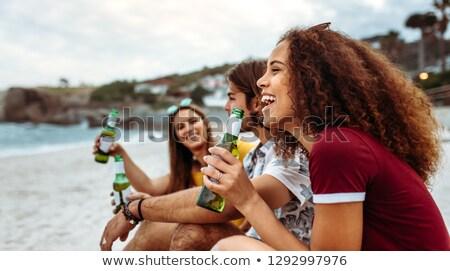 Vista laterale amici bere birra spiaggia Foto d'archivio © wavebreak_media