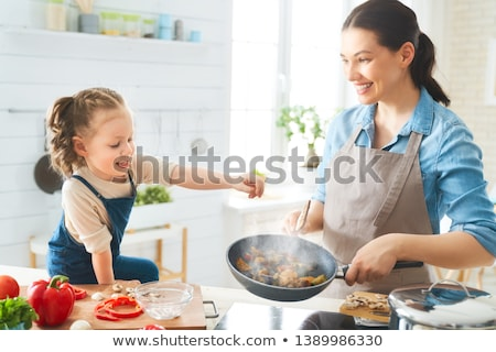 Smiling mother and daughter preparing a salad in kitchen stock photo © wavebreak_media