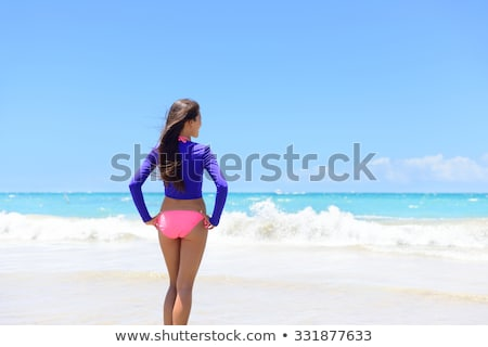 young beautiful woman standing on the beach in swimming suit stock photo © deandrobot