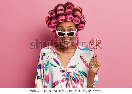 charming woman in sunglasses posing with candy stock photo © deandrobot