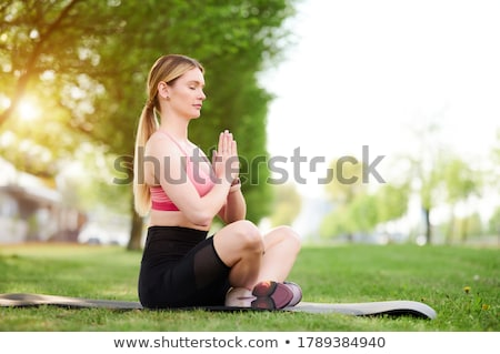 Woman in zen lotos yoga position on grass Stock photo © boggy