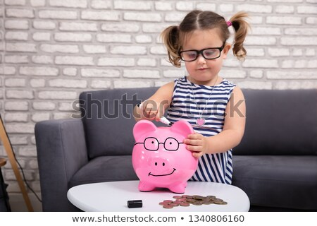 girl painting on piggy bank with marker stock photo © andreypopov