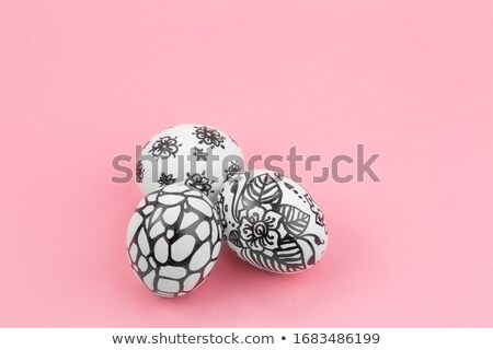 Black and white painted eggs on a black background with copy space. Concept of life change. Flat lay Stock photo © artjazz
