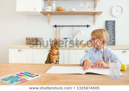 Joyful little happy girl painting and smiling to her bengal cat Stock photo © dashapetrenko