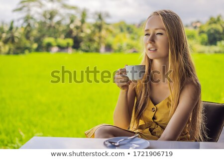 Woman with a cup of coffee on the cafe veranda near the rice terraces on Bali, Indonesia Stock photo © galitskaya
