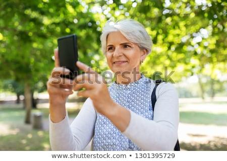 Idős nő fényképezés sejt nyár park Stock fotó © dolgachov
